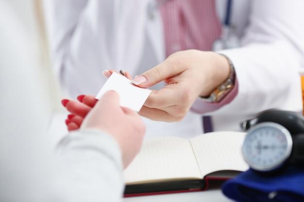 La mano femminile del medico dà lo spazio in bianco bianco