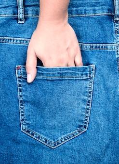 La mano femminile è bloccata nella tasca posteriore dei blue jeans