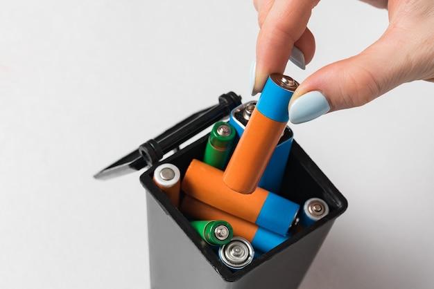 La mano femminile getta la batteria usata nella spazzatura. raccolta e riciclaggio del concetto di batterie usate.