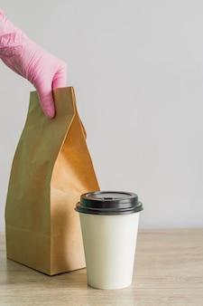 La mano femminile in guanti medici rosa protettivi offre cibo da asporto. concetto di servizio di consegna durante la pandemia di coronavirus