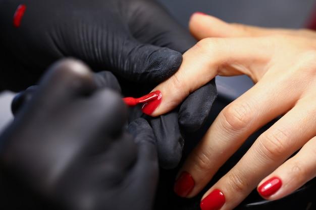 La mano femminile in guanti protettivi neri fa il primo piano del manicure