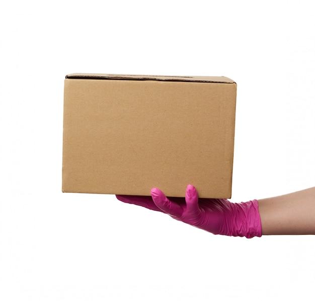 La mano femminile in guanto di lattice rosa contiene una scatola di cartone di carta kraft marrone