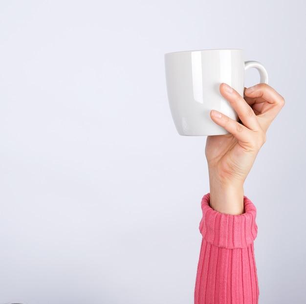 La mano femminile in un maglione rosa tiene una tazza di ceramica grigia, superficie bianca