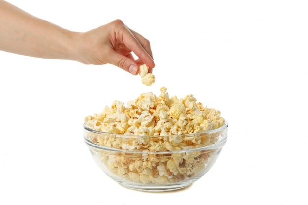 La mano femminile prende il popcorn dalla ciotola, isolata su spazio bianco