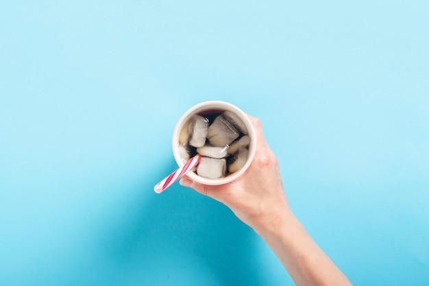 La mano femminile prende o tiene un bicchiere con un rinfrescante caffè ghiacciato su una superficie blu. concetto di calore, sete, cola con ghiaccio. vista piana, vista dall'alto