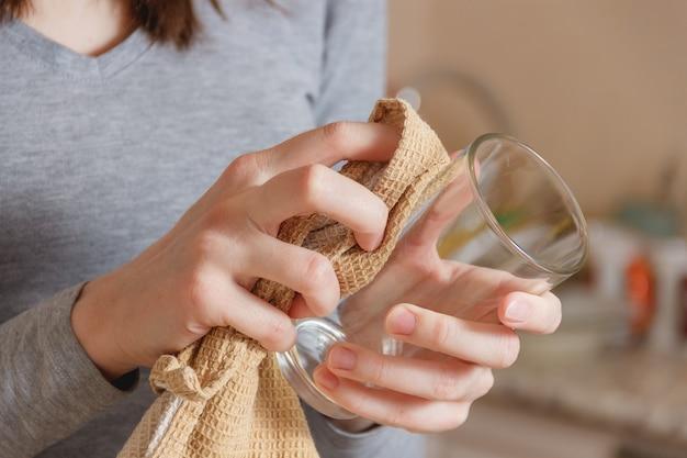 La mano femminile pulisce il vetro pulito per rubinetto in cucina.
