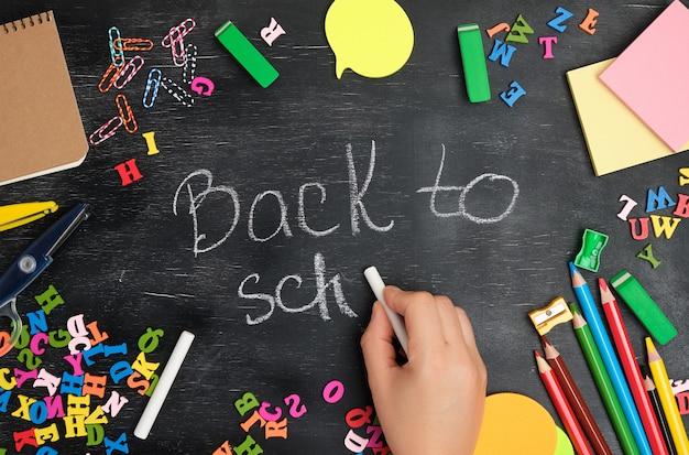 La mano femminile scrive con un gesso bianco su una lavagna di nuovo a scuola
