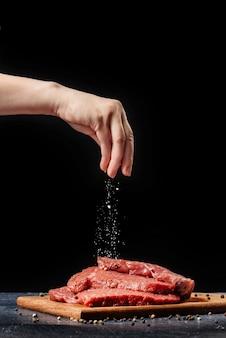 La mano femminile spruzza il sale sulla bistecca di manzo.