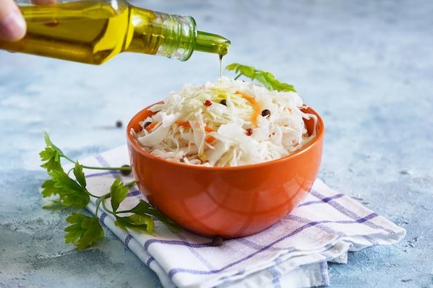 La mano femminile spruzza l'olio d'oliva sui crauti in una ciotola. alimento probiotico sano