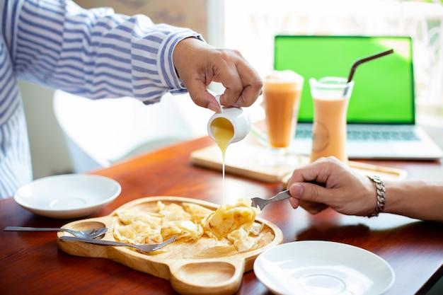 La mano femminile sta versando il latte sul roti croccante della pasticceria