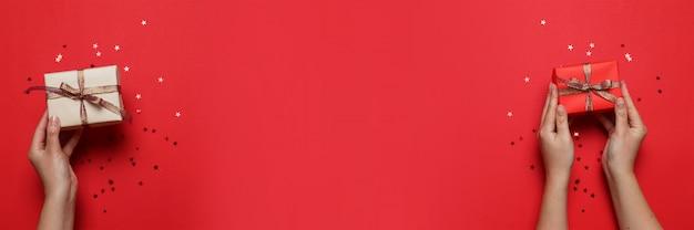 La mano femminile tiene il contenitore di regalo di sorpresa in carta del mestiere e nastro variopinto del raso su fondo rosso con copyspace
