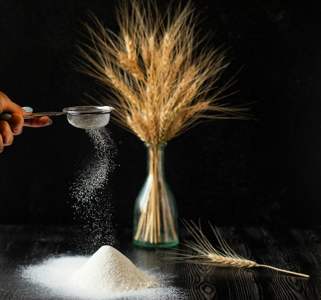 La mano femminile tiene il setaccio e dissipa la farina perfetta