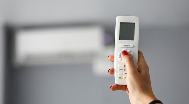 La mano femminile tiene il telecomando per il primo piano del condizionamento d'aria