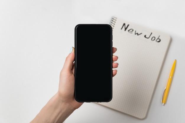 La mano femminile tiene il telefono. penna e taccuino con parole nuovo lavoro.