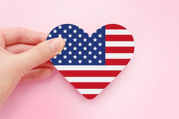 La mano femminile tiene la bandiera di carta a forma di cuore americana isolata sopra spazio rosa, il 4 luglio festa dell'indipendenza dell'america