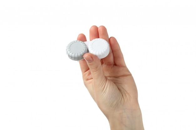 La mano femminile tiene la custodia per lenti a contatto, isolata sulla superficie bianca