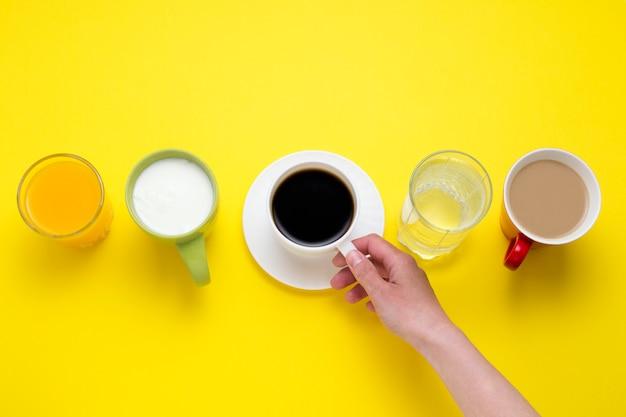 La mano femminile tiene la tazza con caffè nero da una serie di bevande succo d'arancia, caffè con latte, solo acqua, yogurt su uno sfondo giallo. vista piana, vista dall'alto