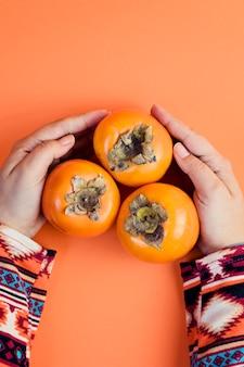 La mano femminile tiene tre cachi maturi sull'arancia.