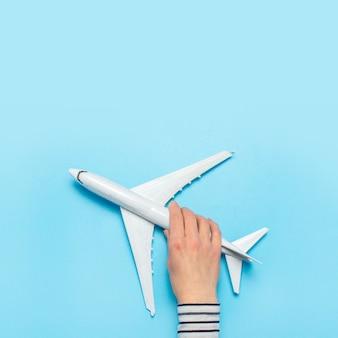 La mano femminile tiene un aereo su un blu. concetto di volo, biglietti, prenotazione, ricerca di voli, viaggi.