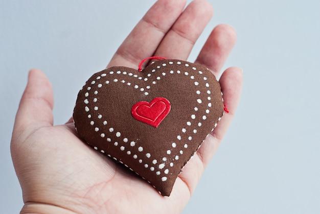 La mano femminile tiene un bellissimo cuore morbido fatto a mano