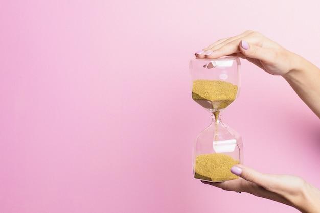 La mano femminile tiene un bicchiere di sabbia su una superficie rosa