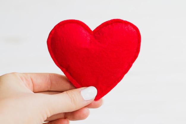 La mano femminile tiene un cuore rosso su una priorità bassa bianca. concetto di san valentino