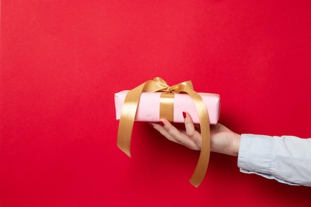 La mano femminile tiene un involucro di regalo avvolto in carta rosa e un arco del nastro dell'oro su rosso