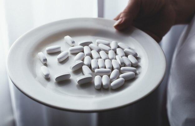 La mano femminile tiene un piatto con le pillole