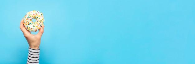 La mano femminile tiene una ciambella su un blu. concept pasticceria, pasticceria, caffetteria.