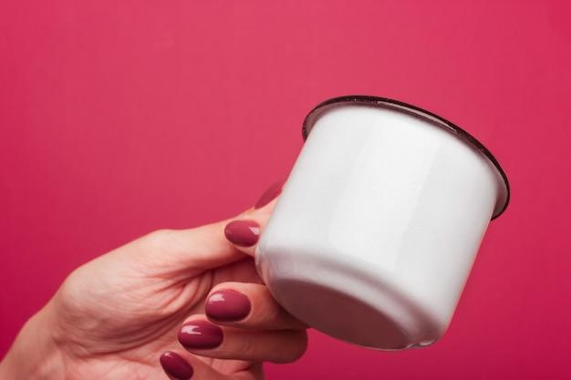 La mano femminile tiene una tazza smaltata bianca con un bordo nero