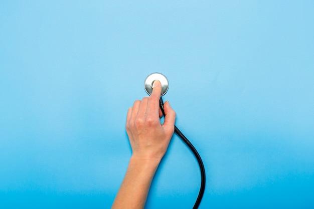 La mano femminile tiene uno stetoscopio su un blu. medico di concetto, appuntamento del medico, virus, trattamento, diagnosi. vista piana, vista dall'alto