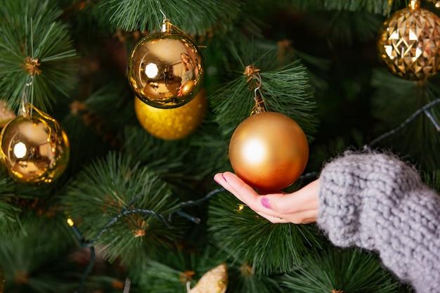 La mano femminile tocca la sfera dorata che pende sull'albero di natale nella stanza. avvicinamento
