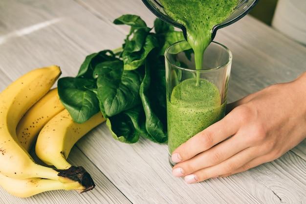 La mano femminile versa un frullato di banana e spinaci in vetro sul tavolo di legno