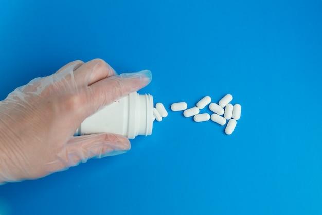 La mano guantata del dottore versa pillole bianche da un barattolo sullo sfondo blu