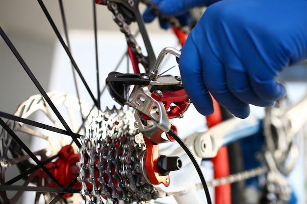 La mano guantata del riparatore regola lo strumento sulla bicicletta