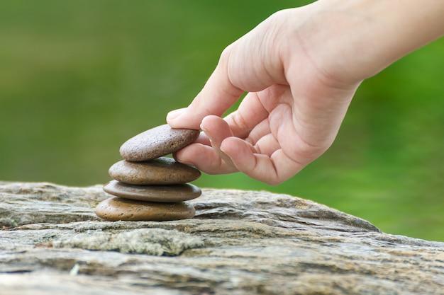 La mano ha messo la pietra costruendo un mucchio di pietre zen
