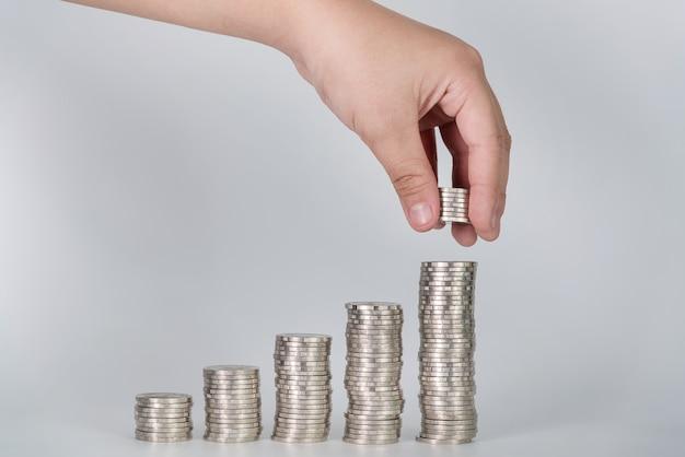 La mano ha messo le monete dei soldi alla pila di monete
