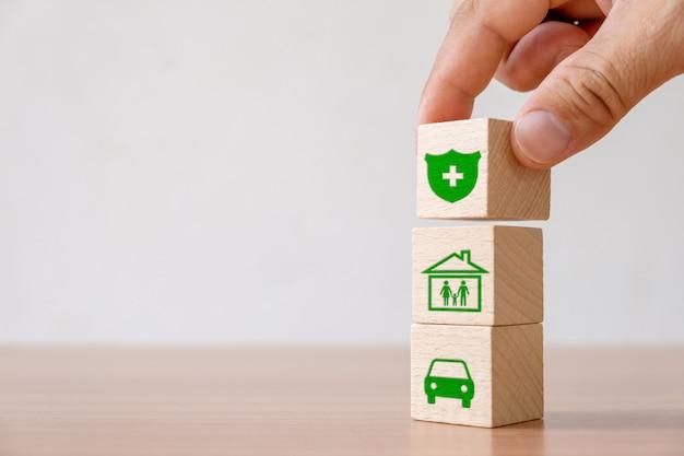 La mano ha scelto il blocco di legno con il segno dell'assicurazione e il simbolo della casa, la famiglia, l'automobile