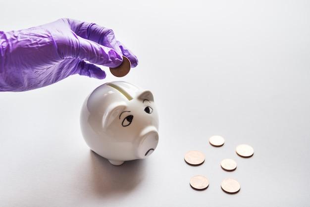 La mano in bagliori mette soldi al salvadanaio triste