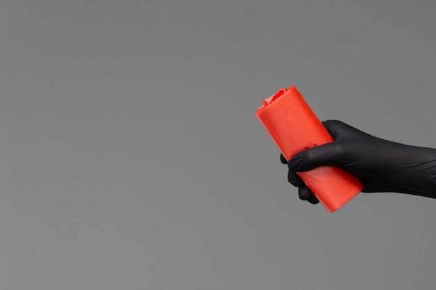 La mano in un guanto di gomma tiene un sacco per la spazzatura colorato