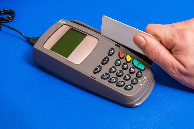 La mano inserisce la carta di credito nel terminale di denaro per il pagamento in banca