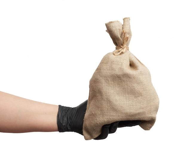La mano maschile in guanto di lattice nero tiene una borsa di tela piena su uno spazio bianco