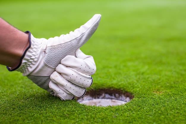 La mano maschile in un guanto da golf mostra ok vicino alla buca