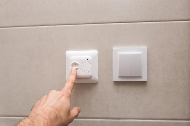 La mano maschile regola la temperatura. il regolatore del riscaldamento di un pavimento isolato termicamente in un bagno.