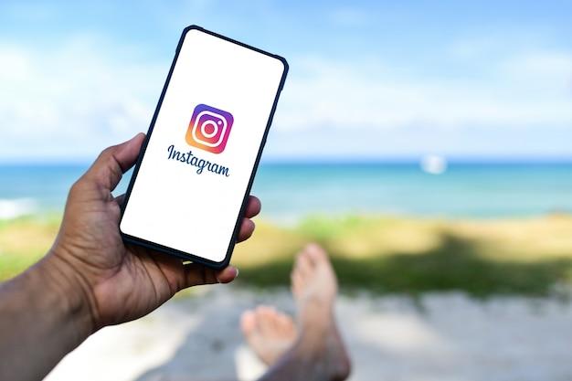 La mano maschile tiene lo smartphone huawei mate 20x che app instagram sullo schermo.