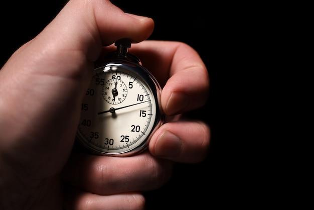 La mano maschio avvia il cronometro analogico su uno sfondo nero, close-up, isolare, copia spazio
