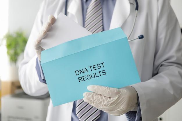 La mano maschio del medico in guanti protettivi bianchi sigilla una lettera di busta dai risultati della ricerca genetica del dna.