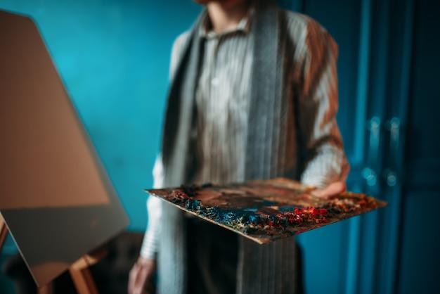 La mano maschio del pittore tiene la tavolozza contro il cavalletto.