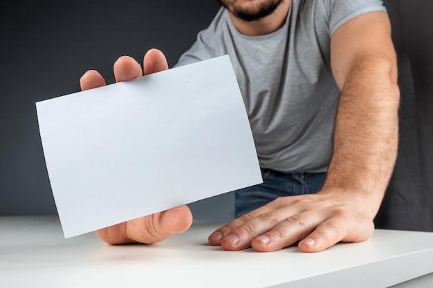 La mano maschio del primo piano tiene una carta bianca, un modello, una disposizione, spazio della copia.