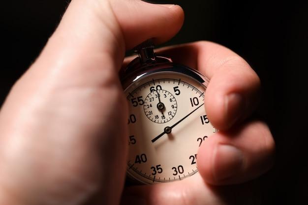 La mano maschio inizia il cronometro analogico su un fondo nero, primo piano, isolato